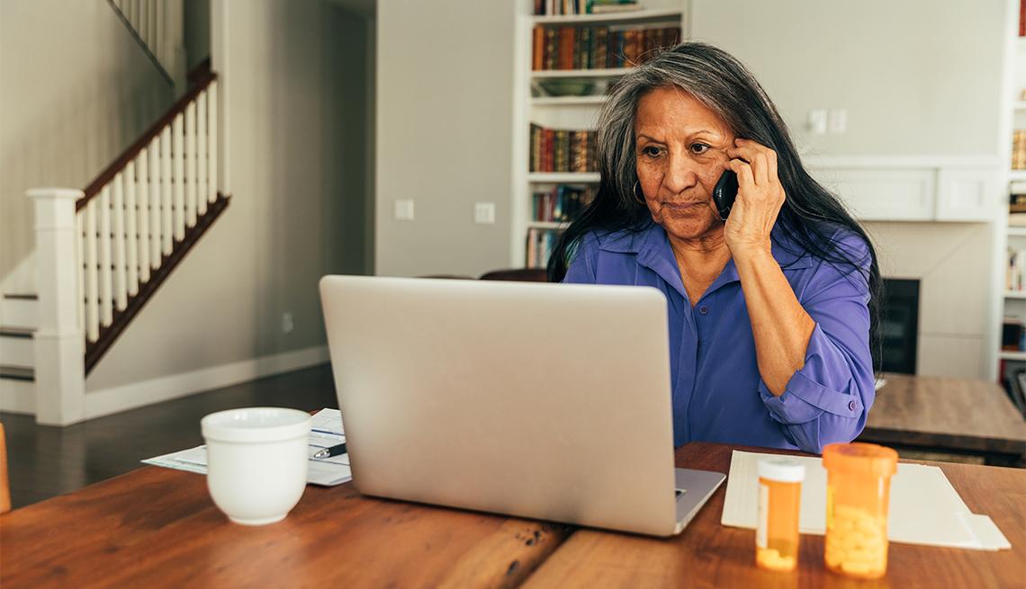 Una mujer sentada frente a una computadora mientras hace una llamada y sobre la mesa tiene medicinas recetadas