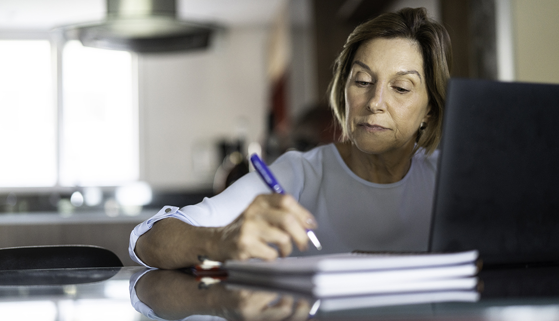 woman looking at laptop and taking notes in notebook on her table