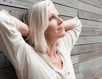 Mujer recostada sobre un muro mirando al cielo - 12 Preguntas para tener en cuenta al seleccionar un Plan Medicare