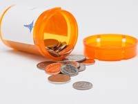 Frasco de pastillas y monedas - Medicare: Subsidio por bajos ingresos para los medicamentos recetados.