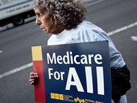 Woman holds sign that reads Medicare for All, options for cutting Medicare costs.
