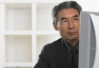 Senior man works on his computer during medicare open enrollment