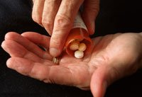 Hands measuring out pills to medicate