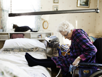 Paraplegic patient Edith Masterman sitting in her wheel chair keeping legs on bed