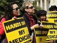 Protesters against cutting Medicare hold signs that read, hands off my medicare.