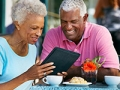 Senior Couple Using Tablet Computer At Outdoor Café, AARP's Medicare Q&A Tool