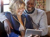 Una pareja usa una tableta digital en casa - Herramienta del Medicare de AARP