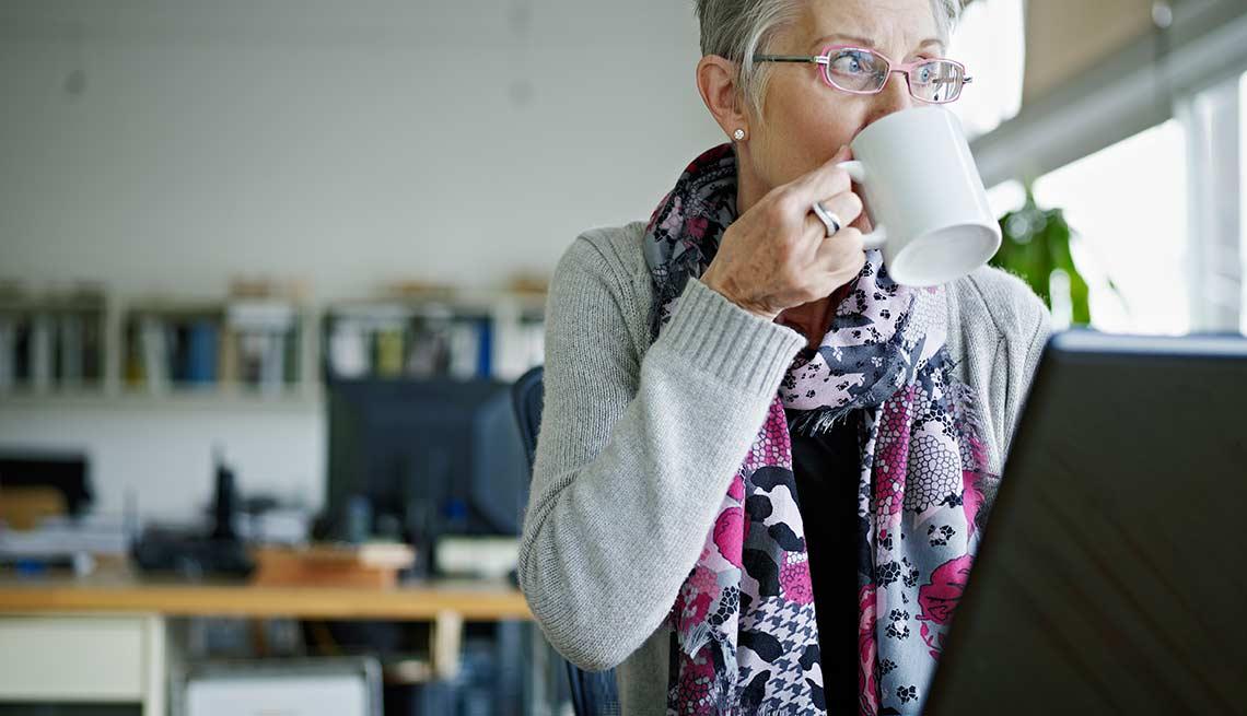 Mujer tomando una taza de café frente a su computadora
