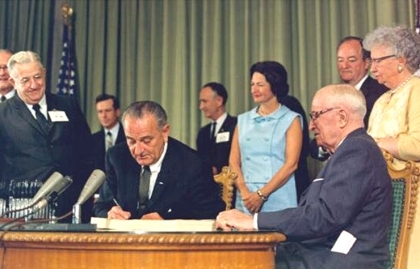 President Johnson signing the Medicare program into law, July 30, 1965. Shown with the President (on the right in the photo) are (left to right) Mrs. Johnson; former President Harry Truman; Vice-President Hubert Humphrey; and Mrs. Truman.