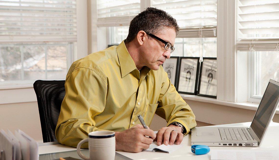 Hispanic man paying bills at desk, Living With Medicare