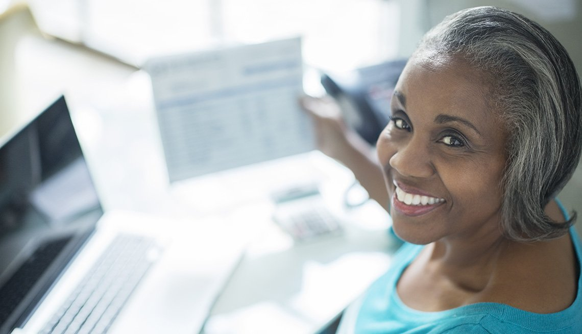 Portrait of smiling woman looking at statements at laptop, Living With Medicare