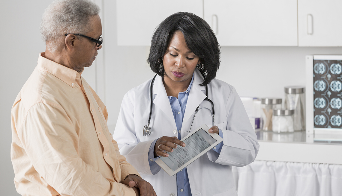 Doctor with patient, Medicare premiums could spike.