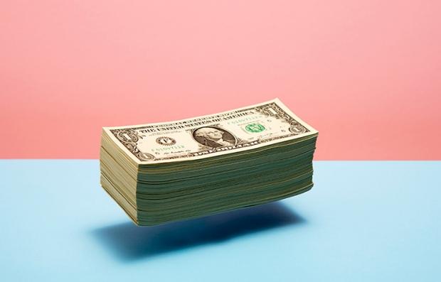 Dinero flotando sobre una superficie azul y fondo rosado