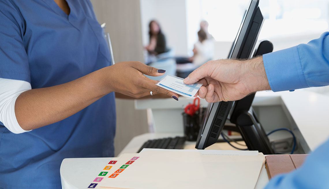 a man handing an insurance card to a nurse