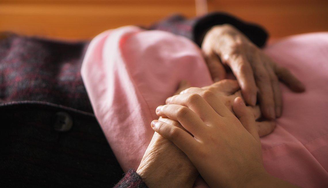 Persona acariciando la mano de una persona mayor acostada