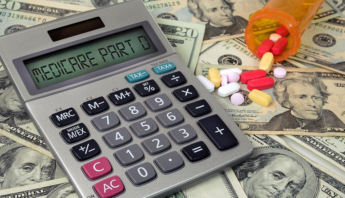 Calculadora sobre dinero y frasco de pastillas derramado