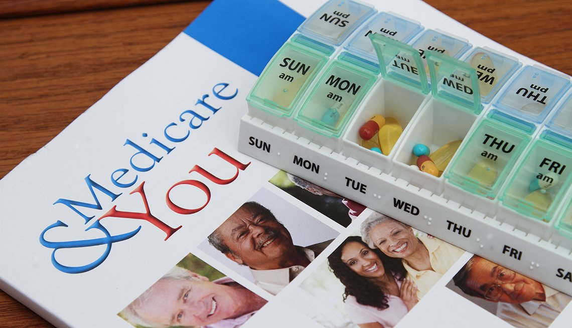 Medicare & You booklet laying on a table. A weekly reminder pill box sits on top.