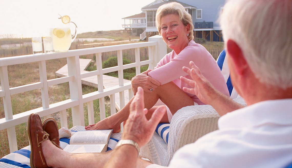 Mature couple talking on the porch of their vacation home