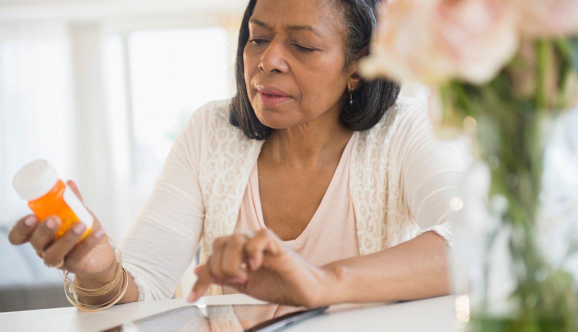 Mujer leyendo las instrucciones en un frasco de pastillas
