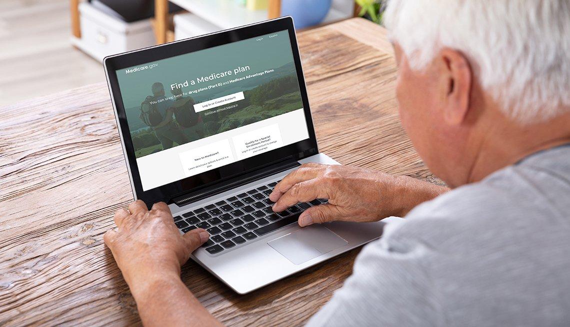 Un hombre busca información sobre Medicare en una computadora portátil