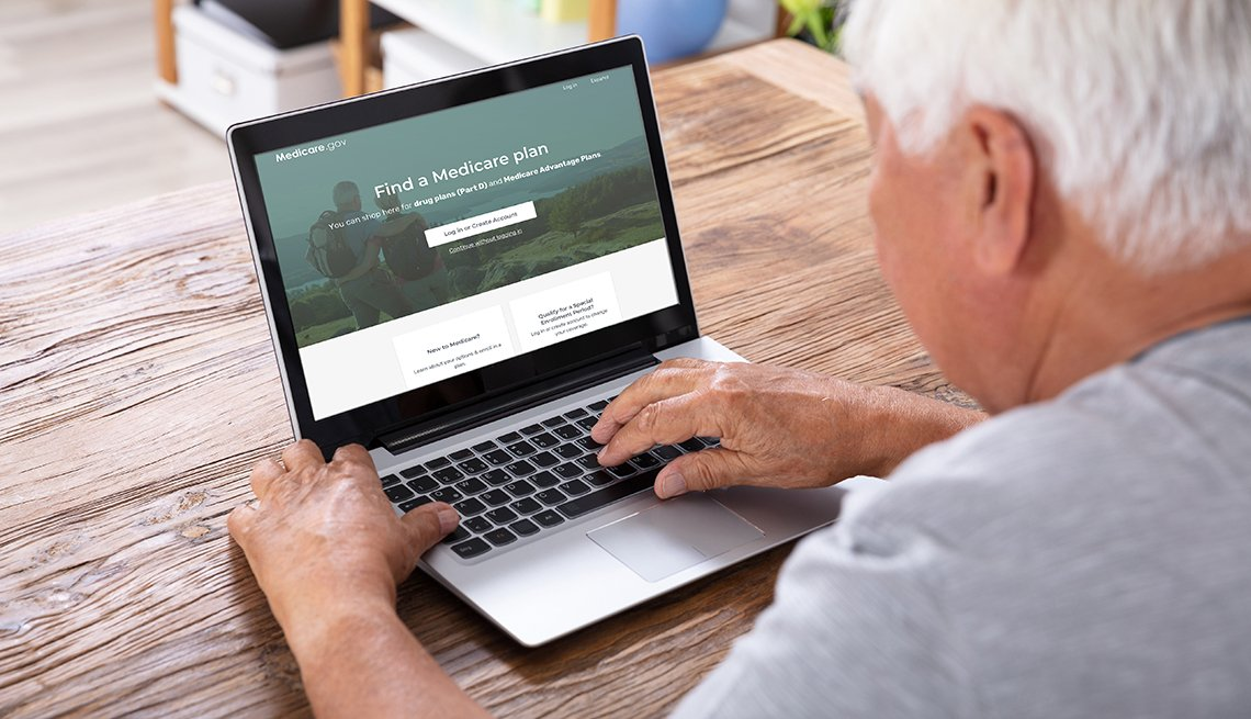 A man sitting in front of a laptop looking at the redesigned Medicare Plan Finder website