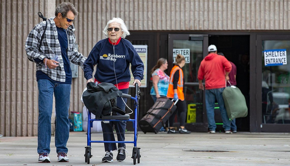 Man helping a woman using a walker outside of a shelter