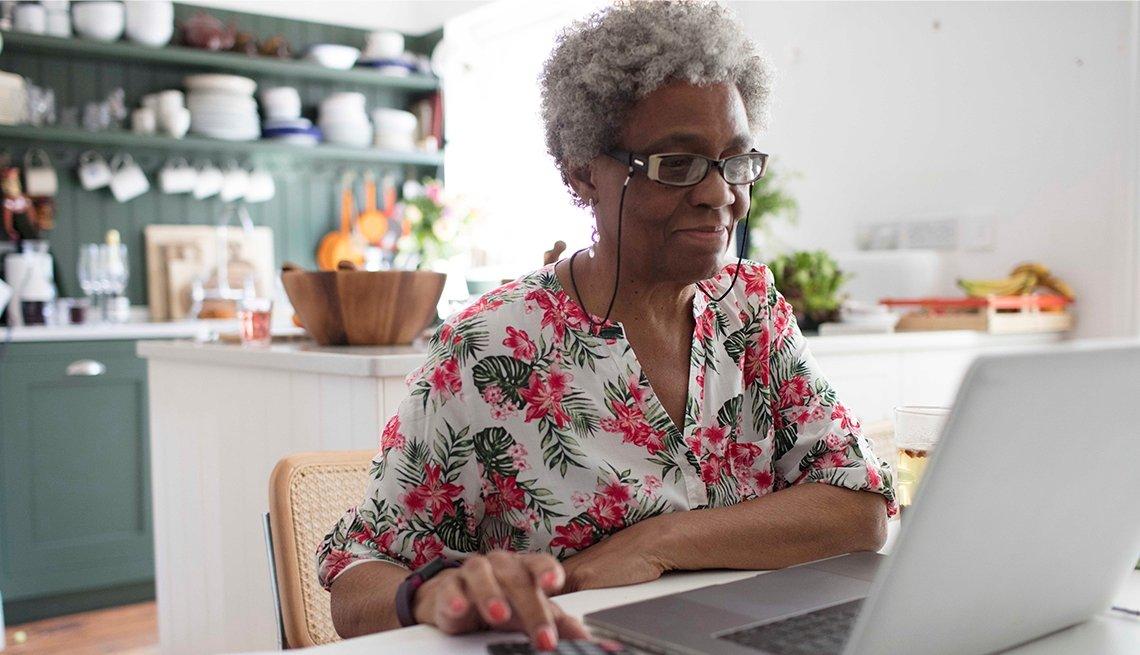 Una mujer frente a su computadora en la cocina de su casa