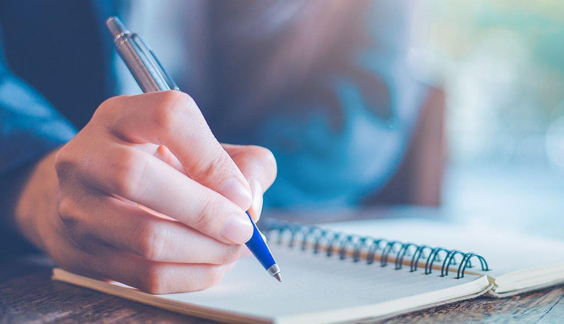 Una persona con un bolígrafo escribiendo en una libreta