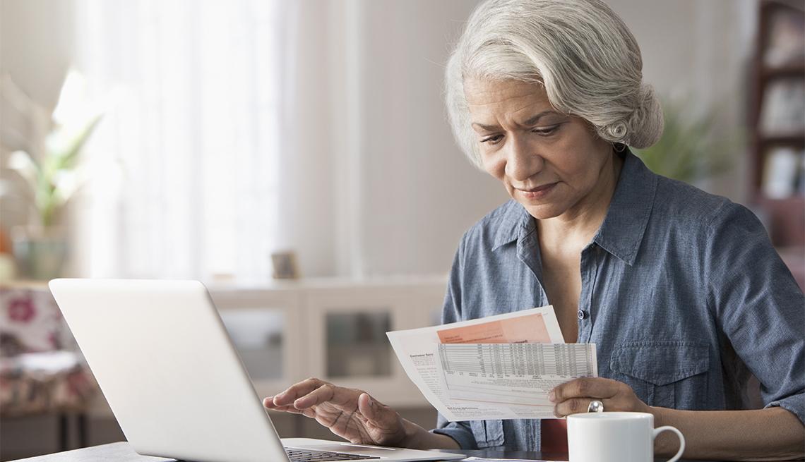 Una mujer frente a su computadora mientras sostiene unas facturas en su mano
