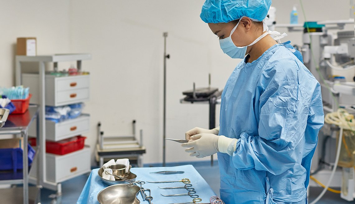 A side view of a female surgeon arranging medical tools on table. Healthcare worker is preparing for surgery. She is wearing scrubs in operating room at hospital