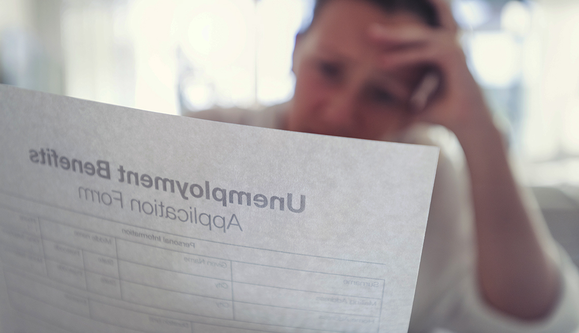 stressed figure in soft focus sits behind a semi-transparent sheet of paper that appears to be an unemployment benefits application form