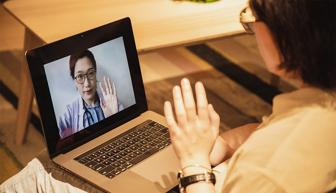 woman consulting doctor on her laptop  holds up her hand for doctor