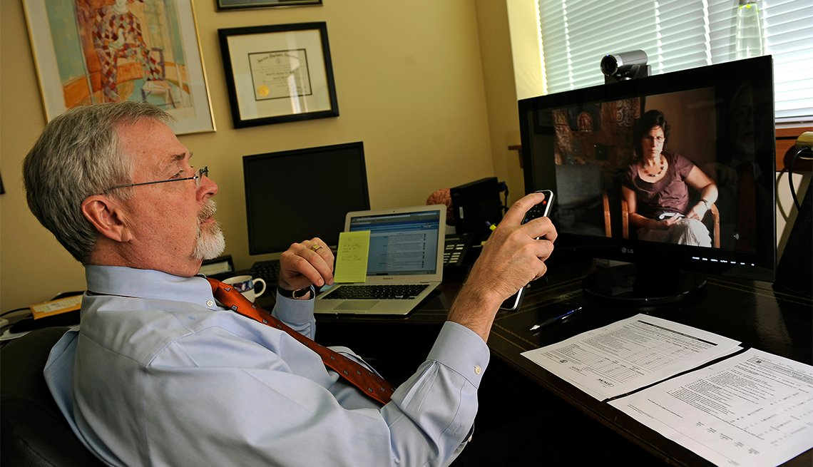 doctor sits at desk in front of large computer screen showing a woman sitting in a chair