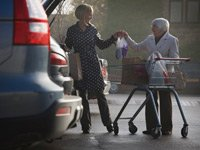 woman helps with another woman's shopping bags, caregiving resource center AARP