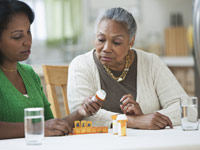Daughter assisting mother with medication - Caregiving Not Easy But Rewarding