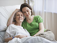 Embracing Mother and daughter in hospital - The emotional side of caregiving
