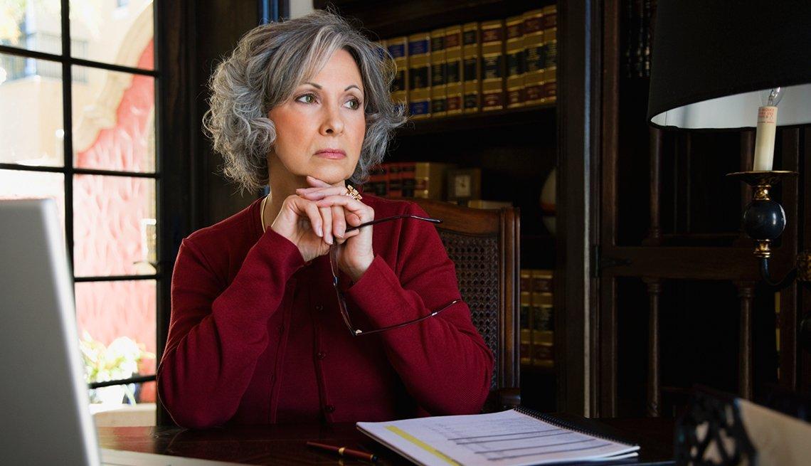 Mujer sentada en su escritorio mirando los formularios de directivas anticipadas.