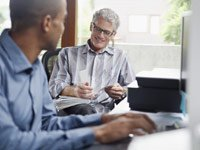 AARP offers advice for working people who must be caregivers too- two people speak in an office