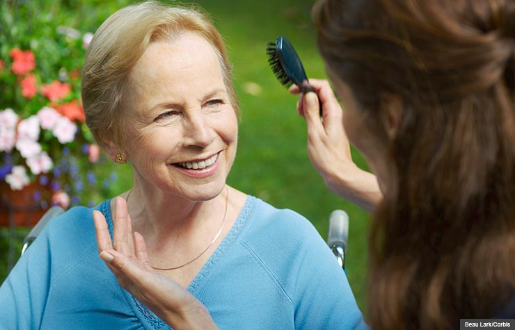Woman brushes hair of senior lady, Solo caregivers are encouraged to take care of themselves and get needed help