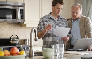 Son talking to father with paper and laptop in kitchen, Health care planning