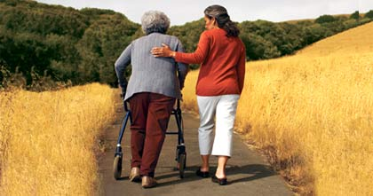 Woman helping woman walk on path-AARP-Caregiving-Resource-Center
