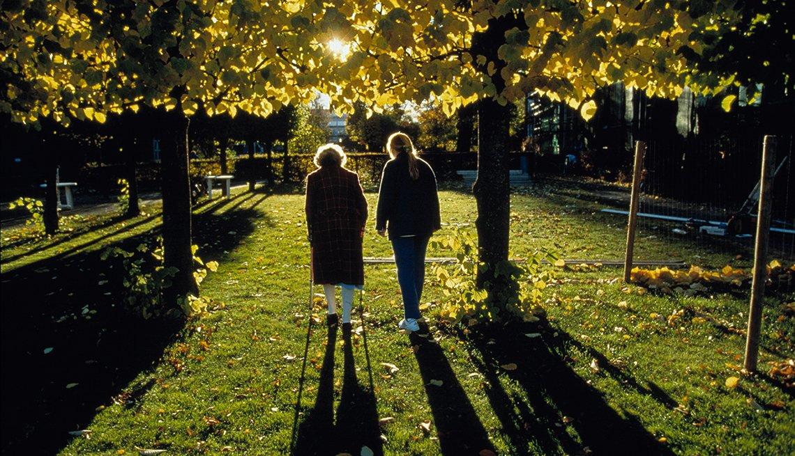 Recomendaciones de AARP para las preguntas correctas al momento de elegir un asilo de ancianos para un miembro de la familia, una enfermera camina con un paciente fuera