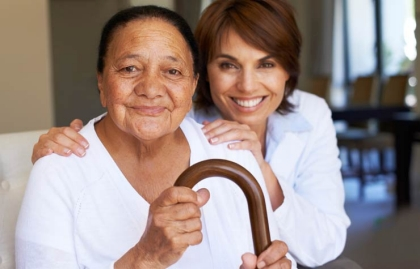 Mujer joven abraza a la mujer mayor con bastón, Caregiving Resouce Center