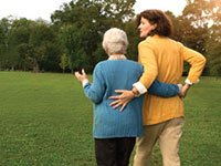 Caregiving Resource Center - mother and daughter walking in park. caregiver resources and information on assisted living and more.