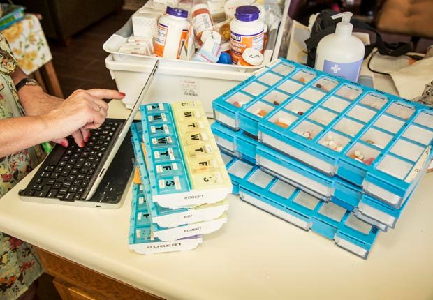Amy refilling pills while working, Juggling Work and Caregiving (Beth Perkins Photography)