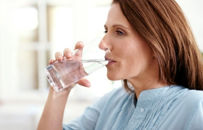 A woman enjoying a glass of cold water