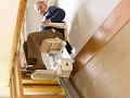 A senior man uses a stair lift in his home