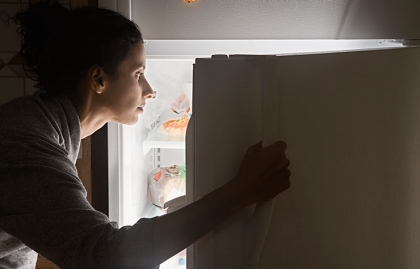 Mujer abriendo un refrigerador de noche - Cómo el insomnio puede llevar a comer en exceso