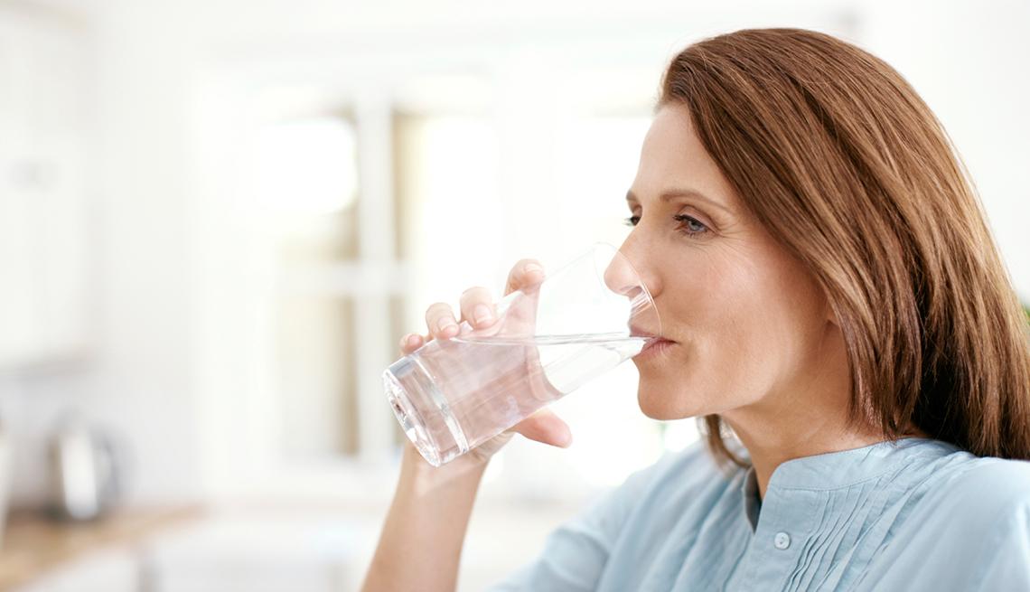 Una mujer tomando de un vaso de agua