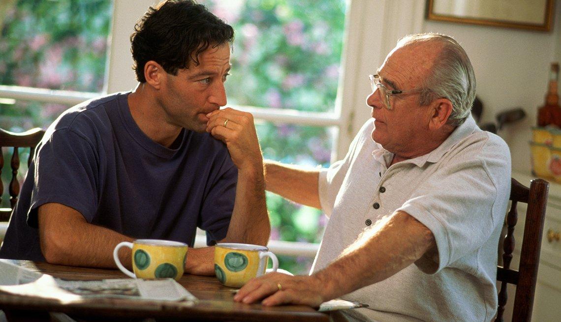 Padre e hijo tomando café y hablando en casa